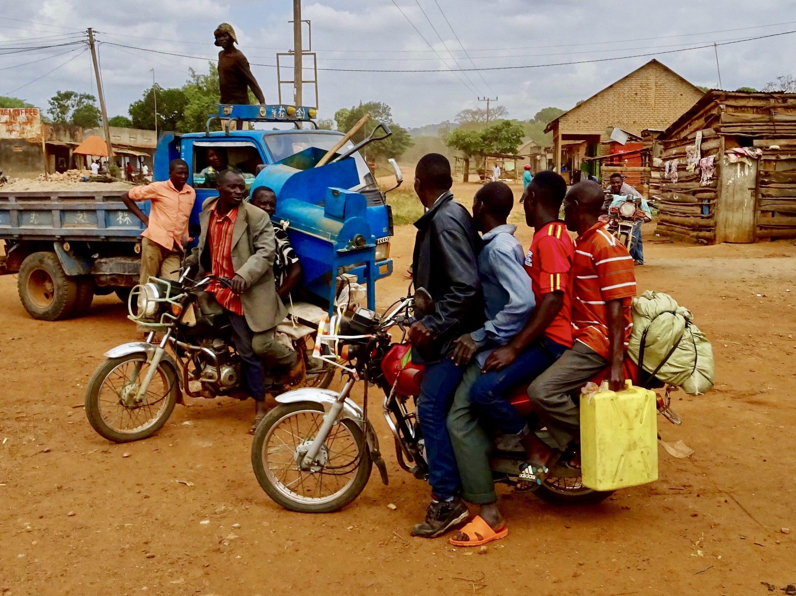 Boda boda's met van alles en nog wat langs weg in Oeganda