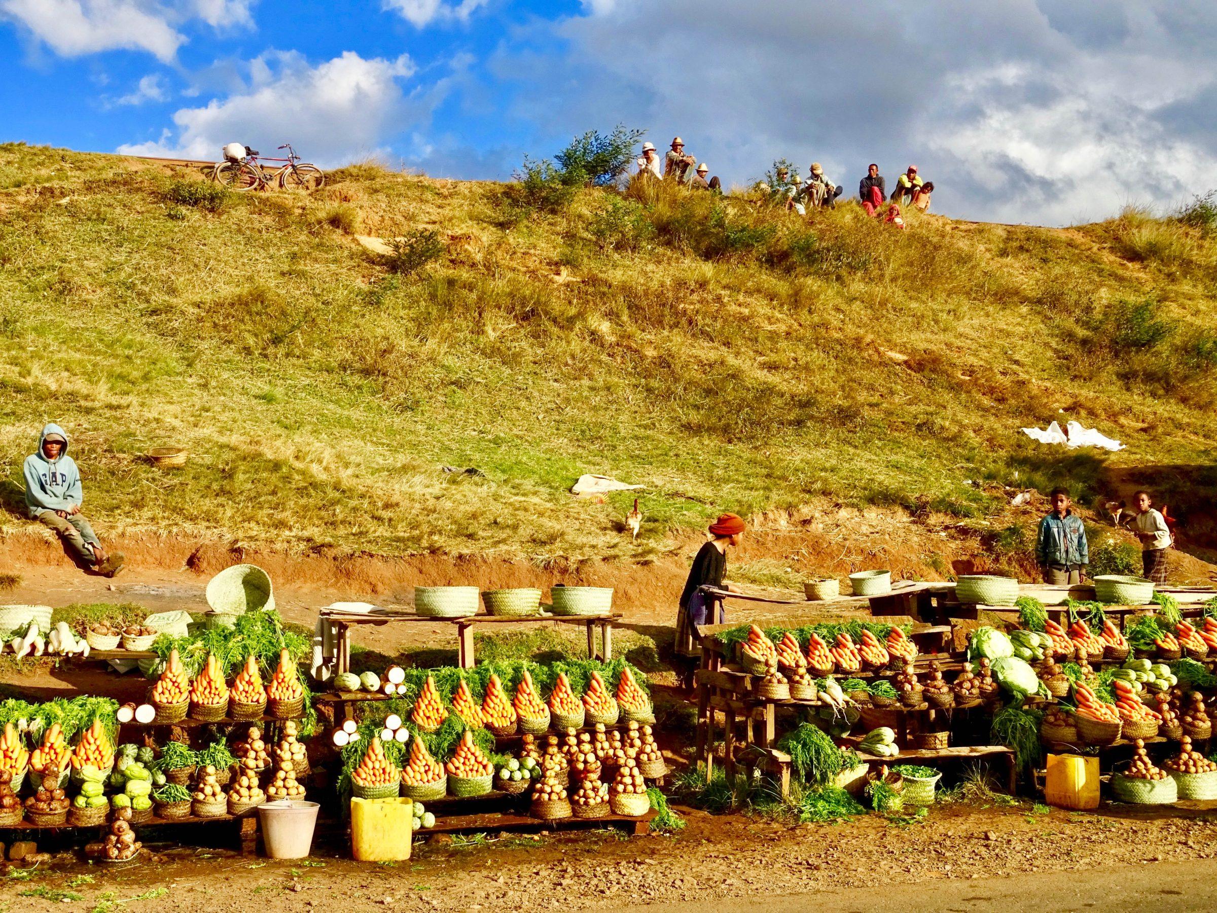 Toeschouwers op de heuvel kijken naar de verkoopsters nabij Ambohimandroso