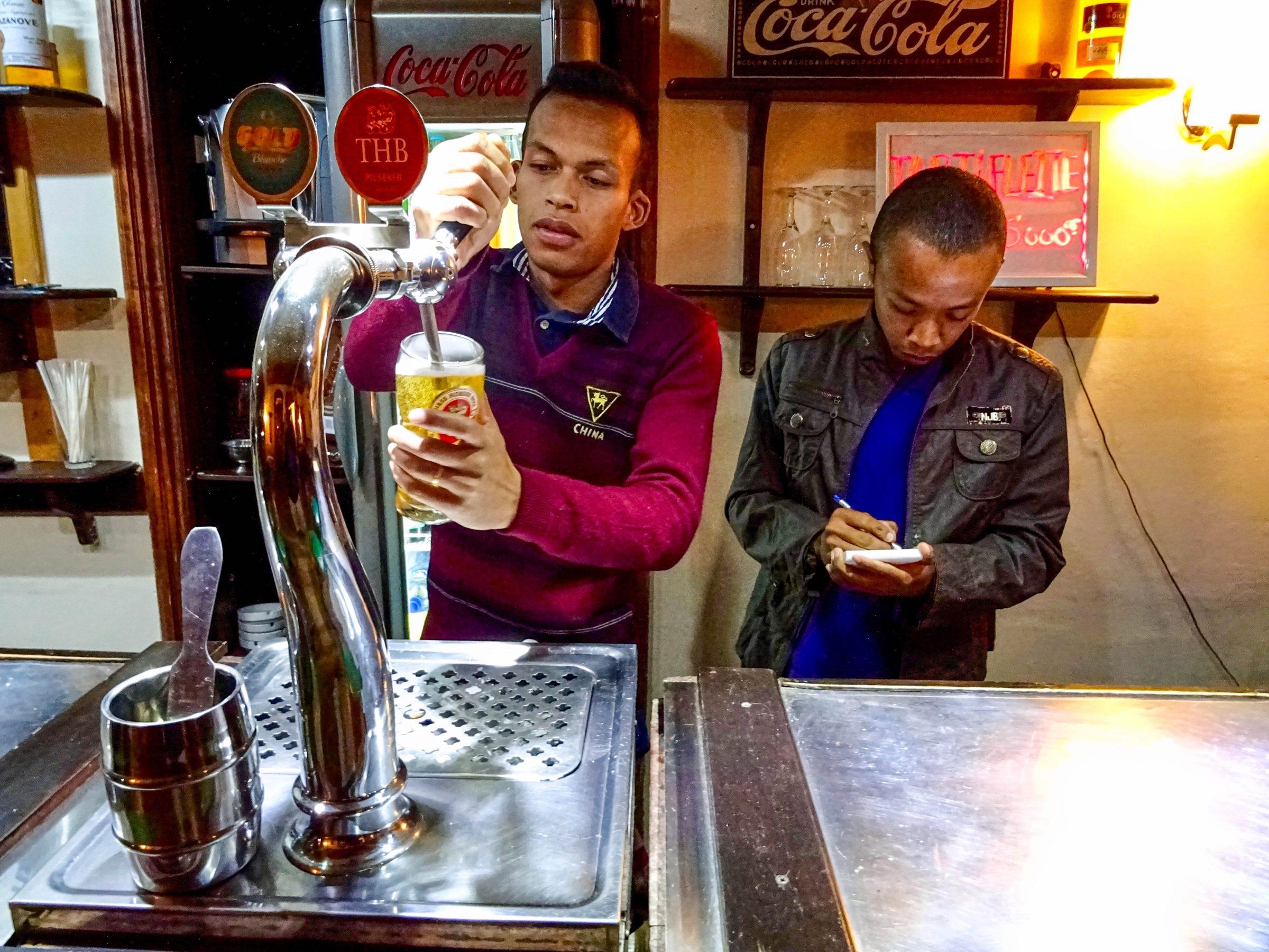 De barman in hotel Le Trianon in Antsirabe tapt een verse Three Horses Beer