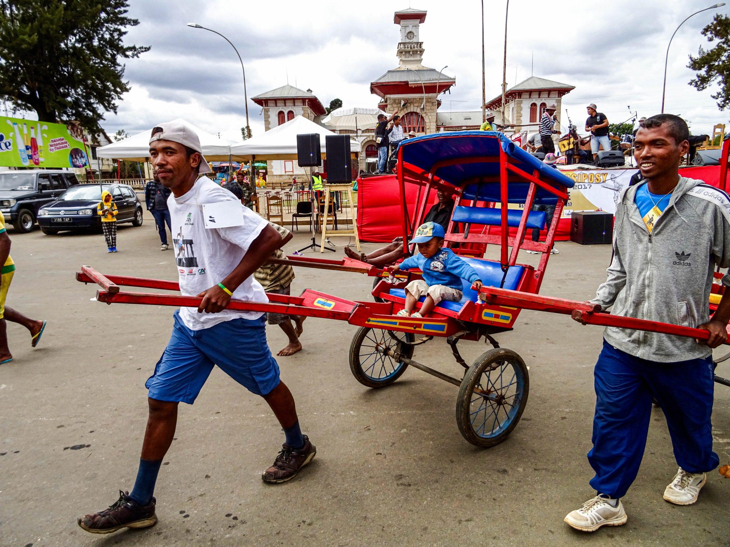 Een jongeman laat zich vervoeren in een pousse pousse in Antsirabe