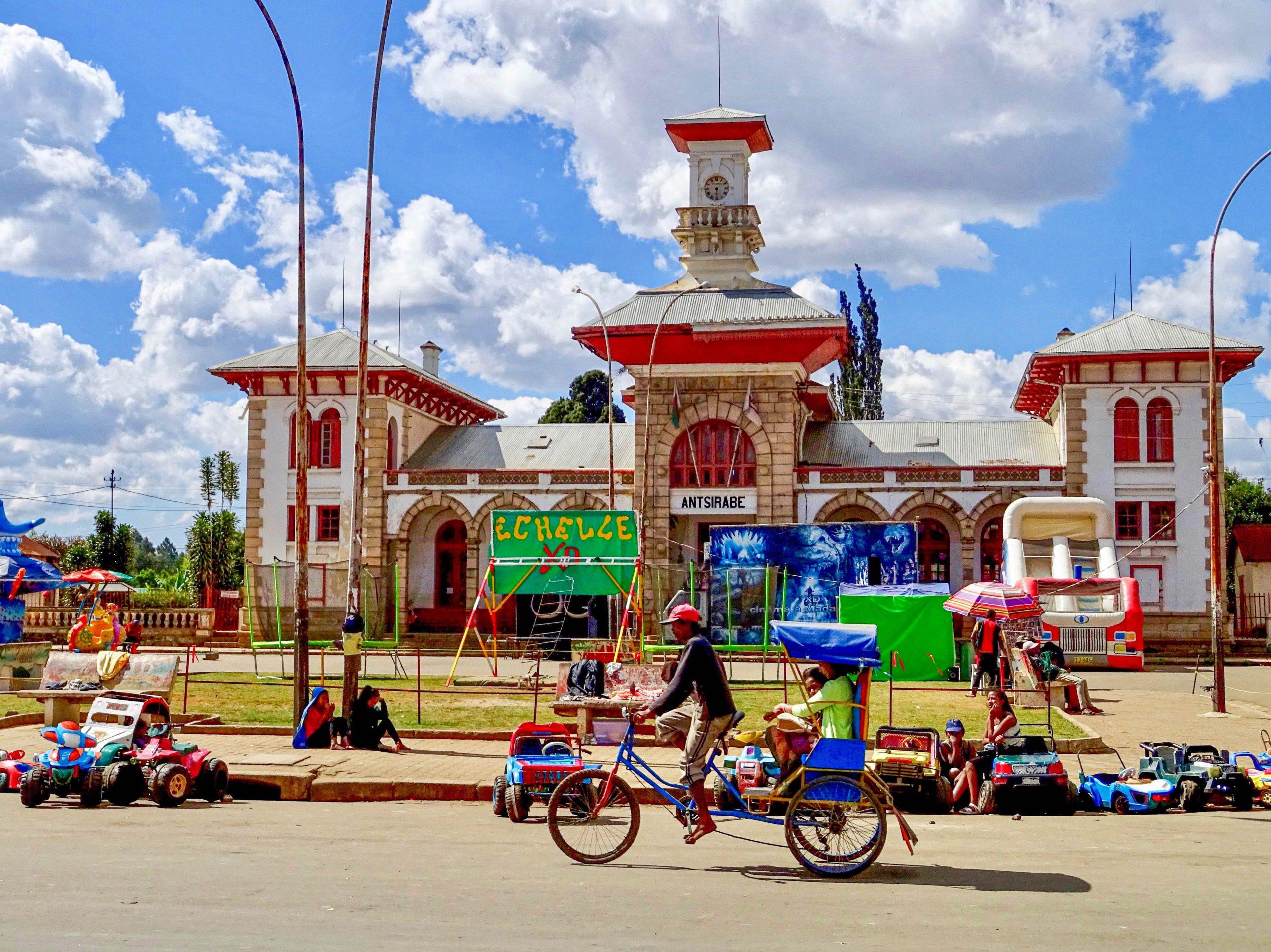 Een pousse pousse voor het voormalige treinstation van Antsirabe