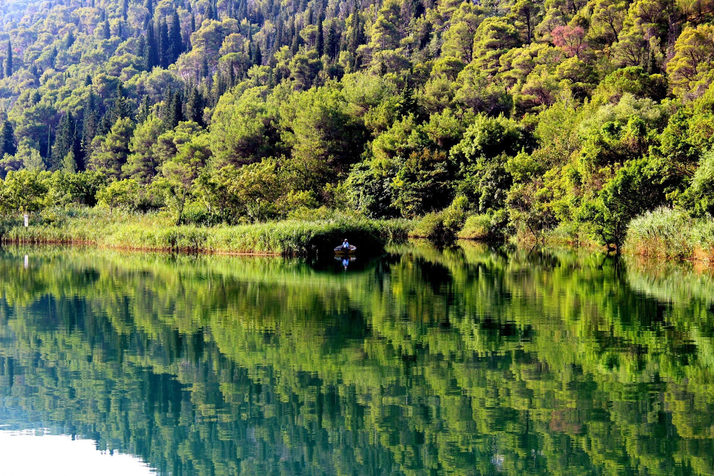 Zes uur 's morgens, een visser op het spiegelgladde water onderweg naar de Krka watervallen