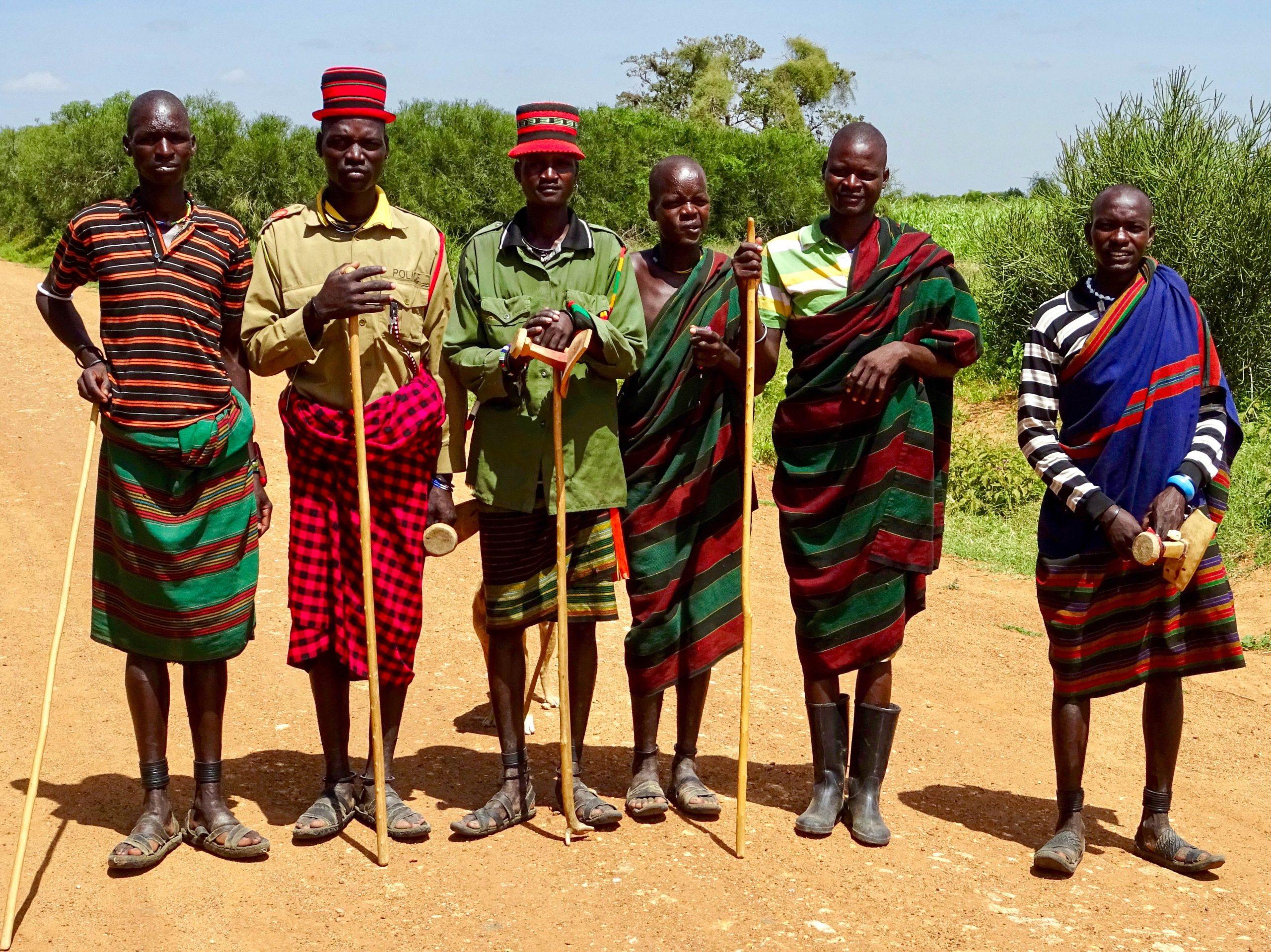 Karamajong herders in traditioneel tenue poseren