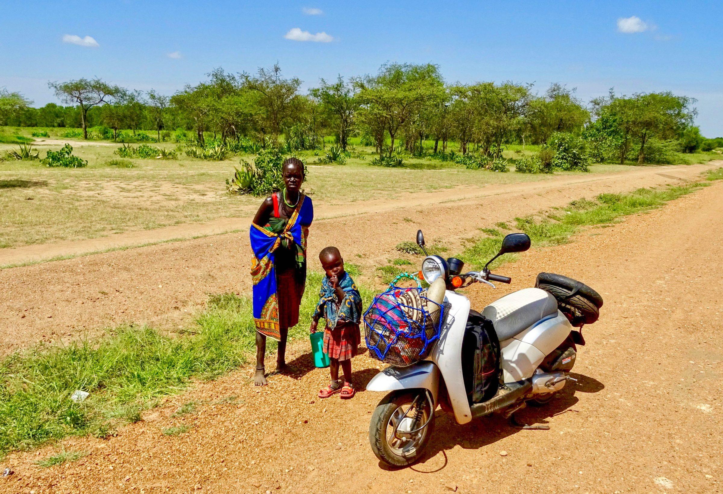 Moeder en dochter Karamajong bewonderen  mijn scooter nabij Amgamwa