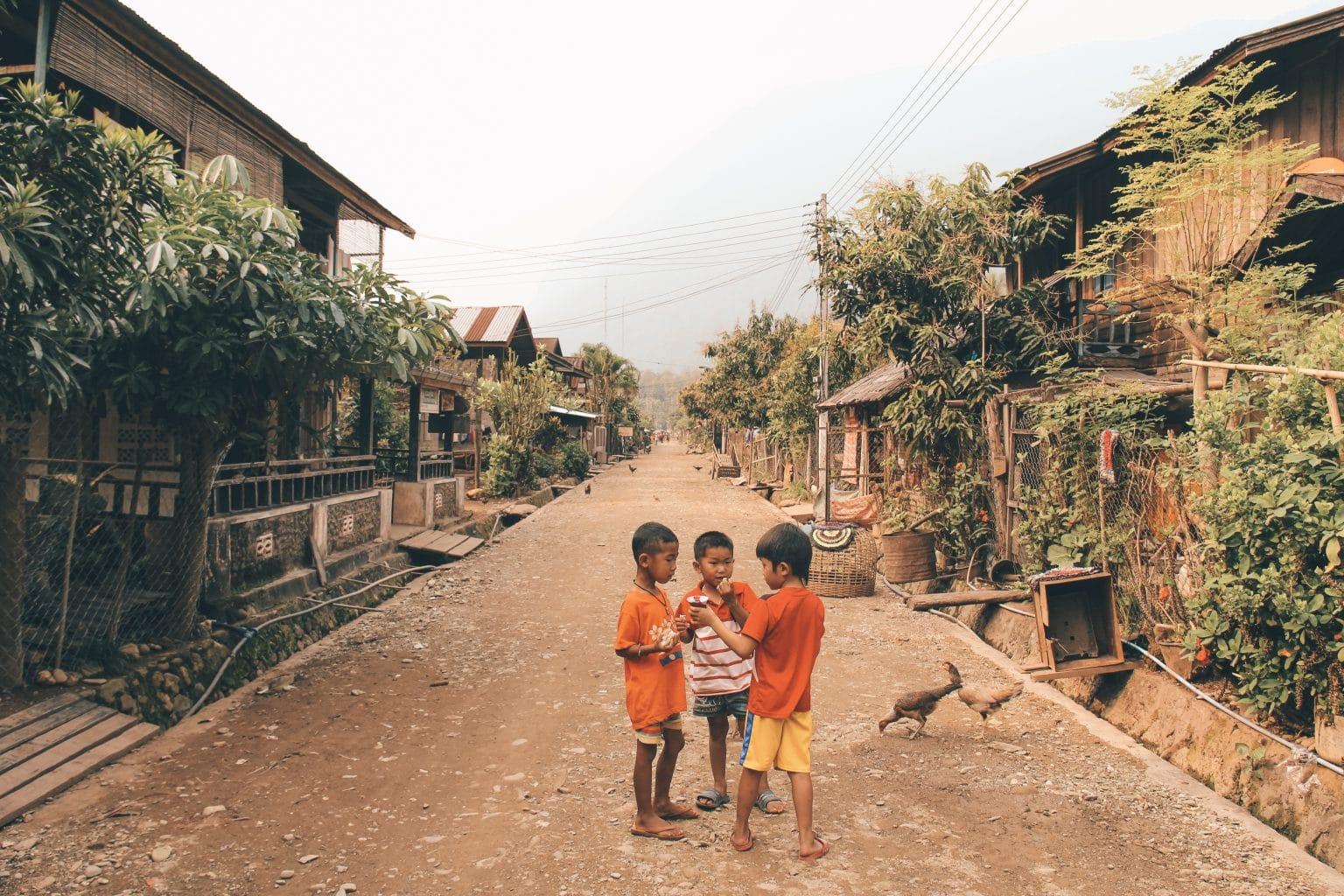 De lange straat van het dorpje Muang Ngoy. Spelende kinderen en kippen all over the place!