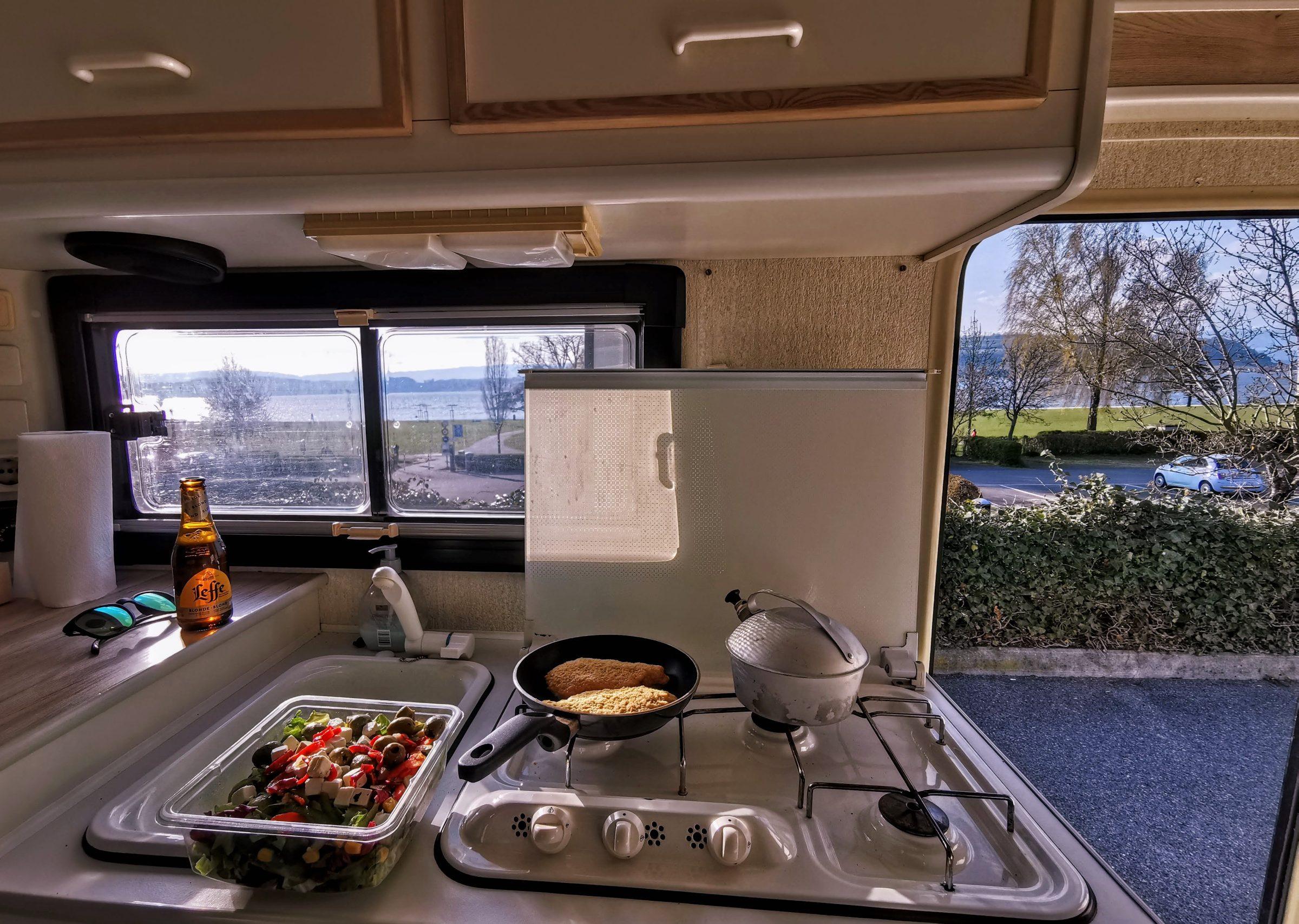 Eten bereiden in de camper met uitzicht op het meer