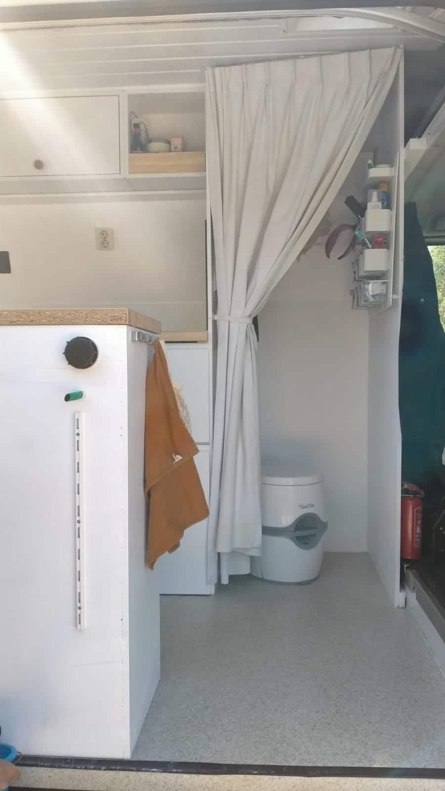 Toilet, een wand met toiletspullen, een spiegel en een droogrek in de camper.