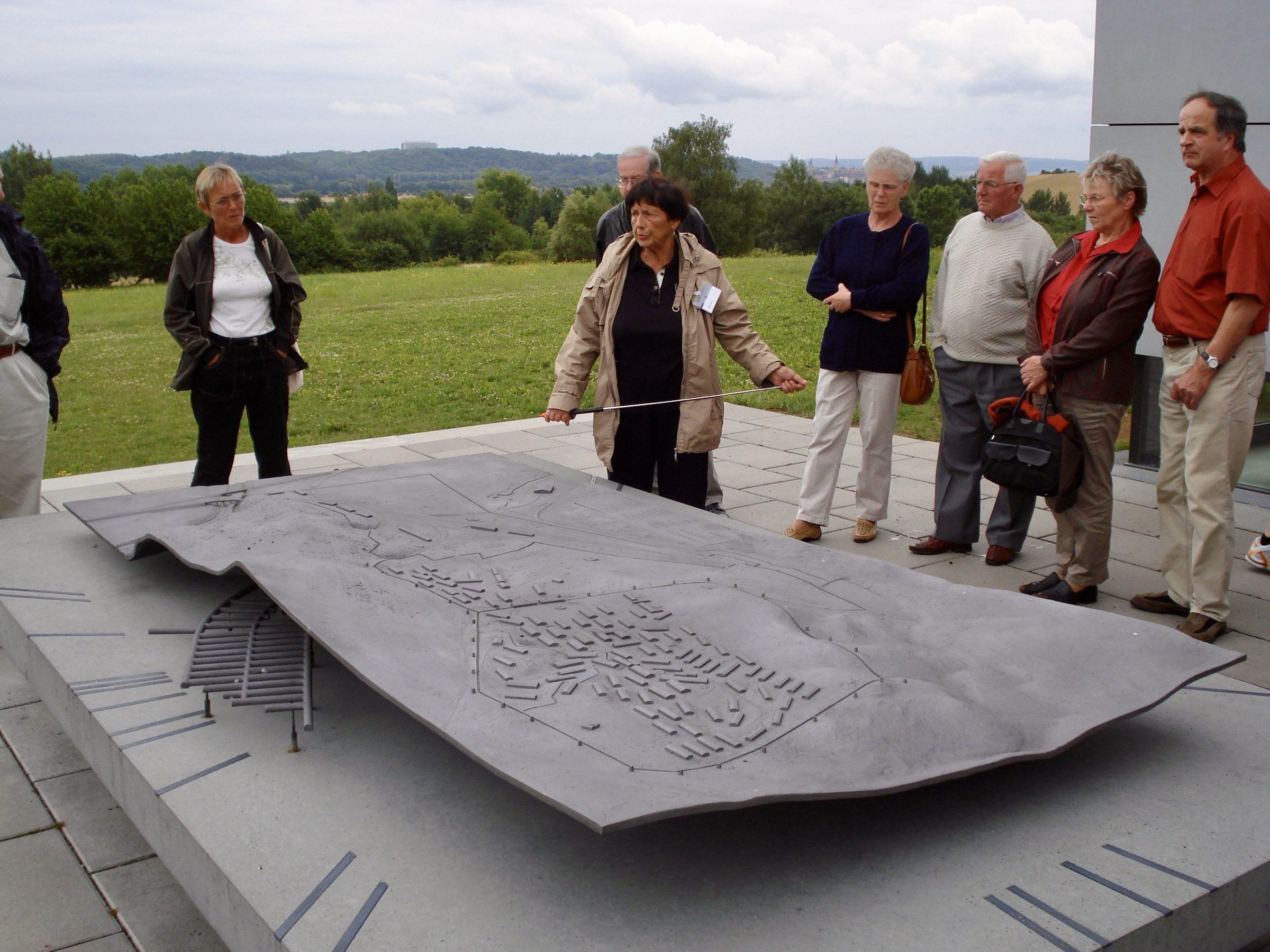 Een gids van het museum Dora/Mittelbau bij de maquette van de gevangenenbarakken