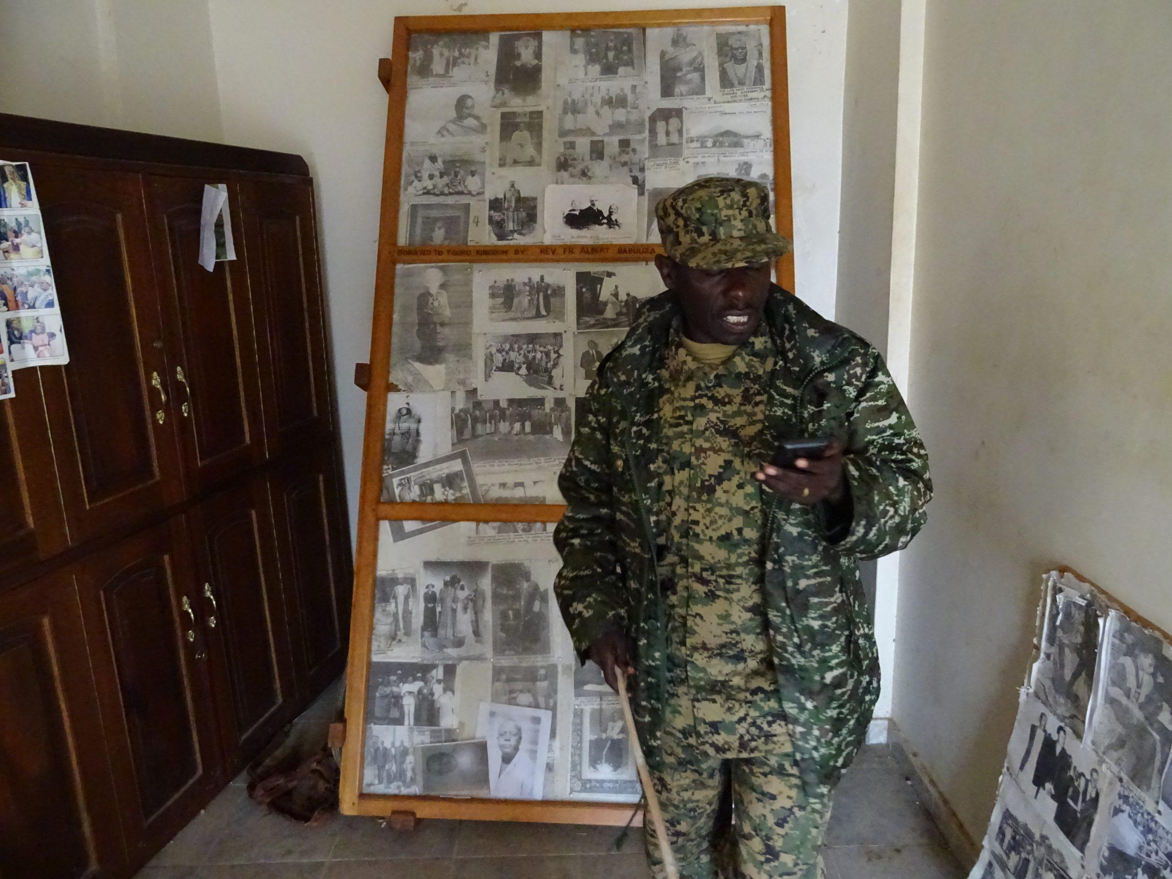 De bewaker in het paleis van Tooro in Fort Portal aan het bellen met zijn schoonmoeder