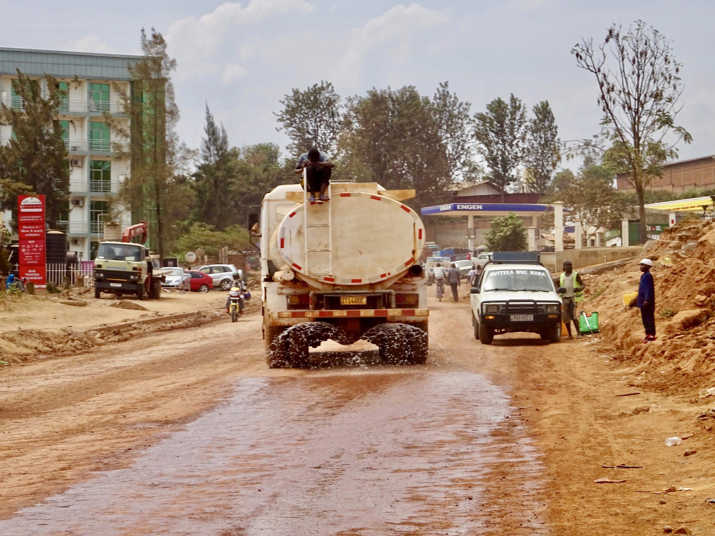 Een tankwagen strooit water op een zandweg in Kigali