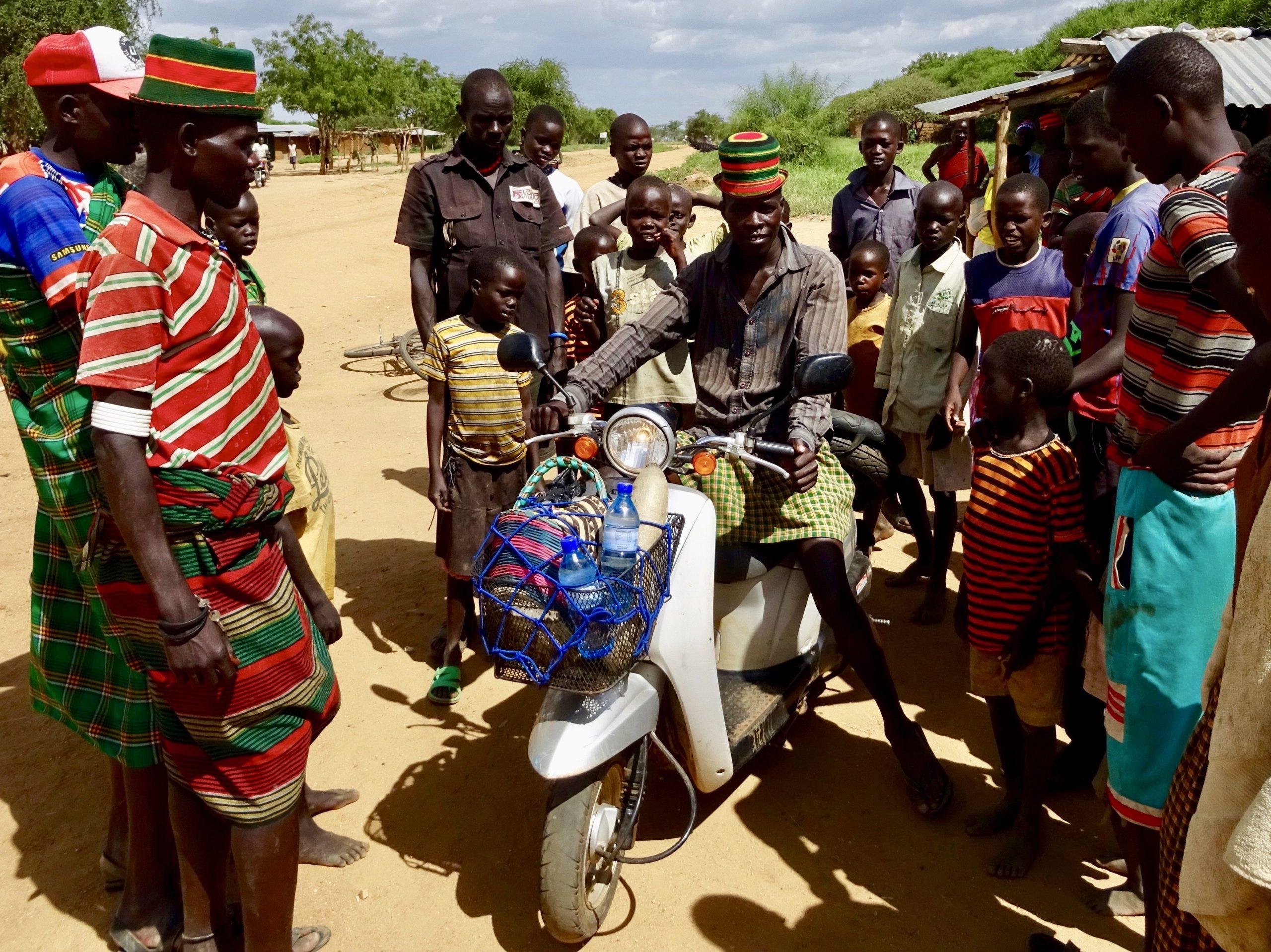 Een Karamojong test mijn scooter in Noord-Oeganda
