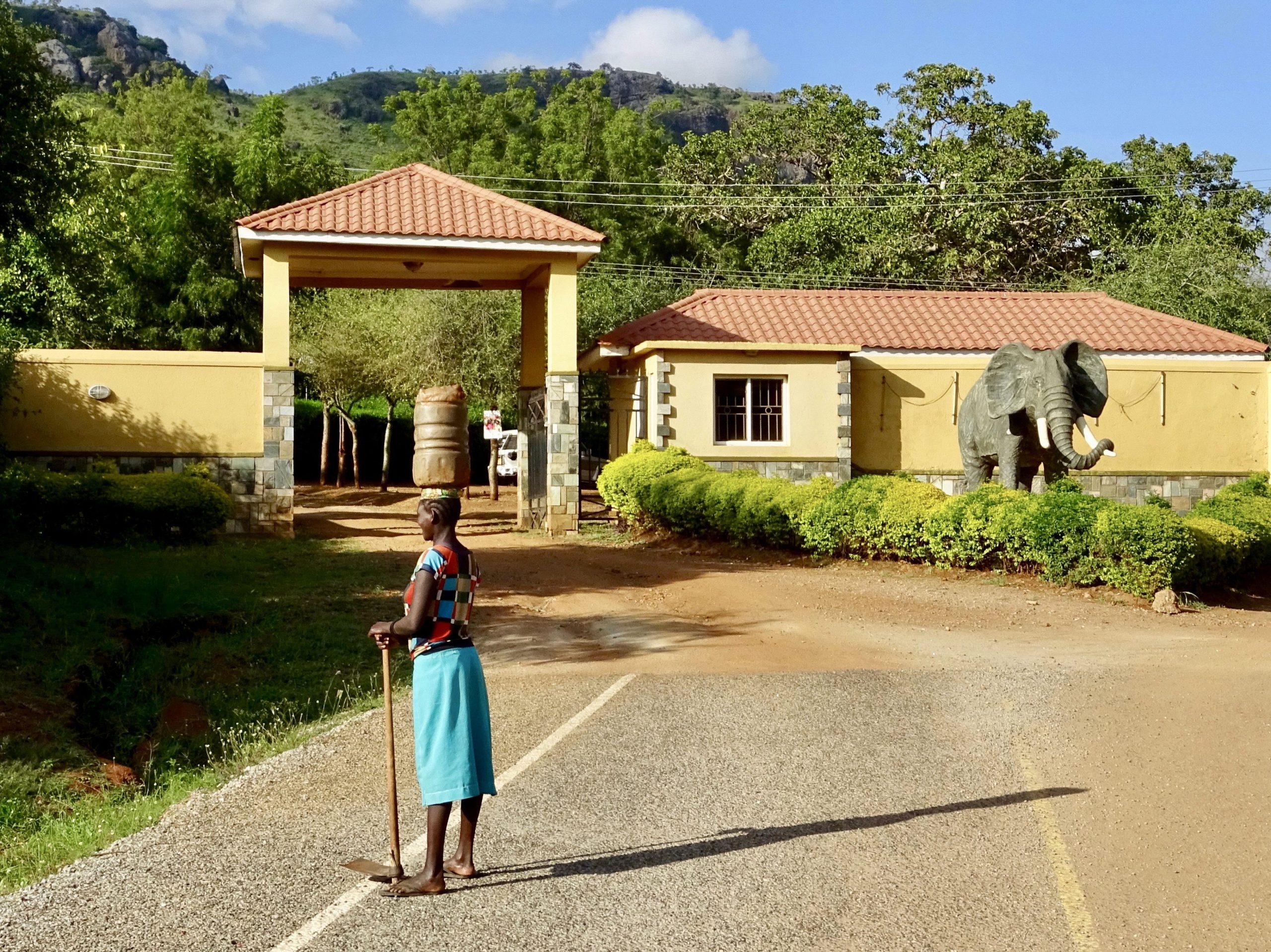 Een vrouw staat gezellig te roddelen voor de entree van Hotel Mount Moroto