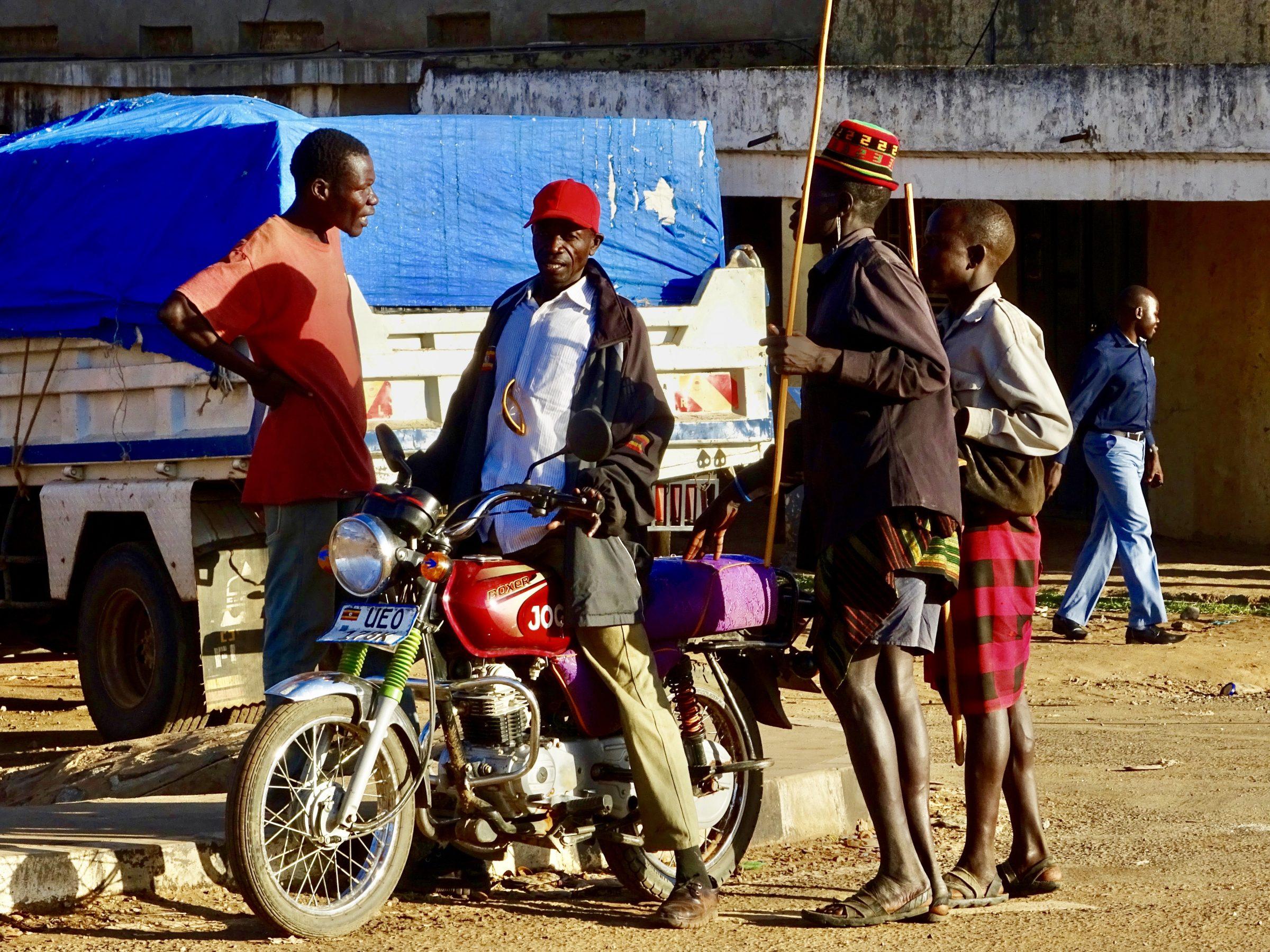 Boda boda chauffeur met twee Karamojong passagiers op de toegangsweg naar Moroto