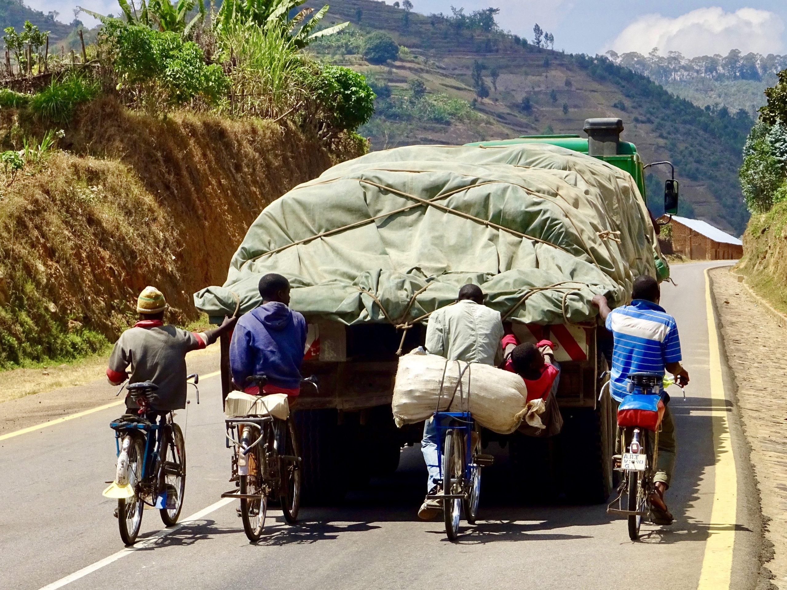 Rwandese fietsers liften mee met een truck de heuvel op