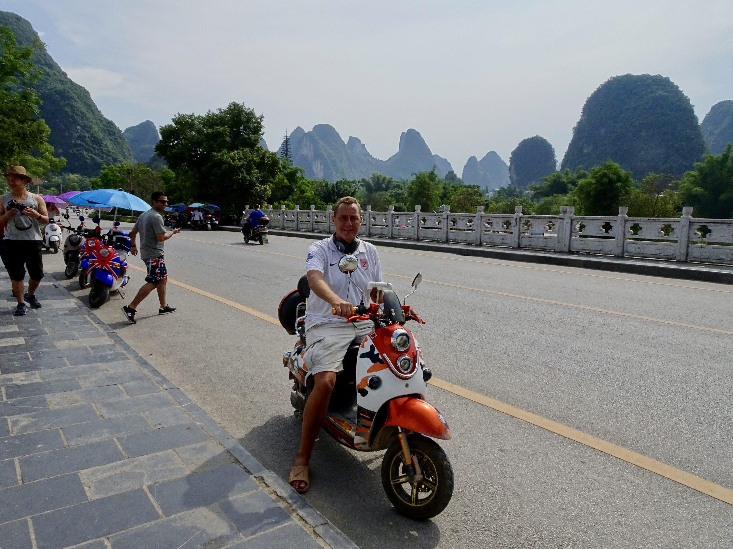 Op een elektrische scooter bij de krijtsteenrotsen van Yangshuo
